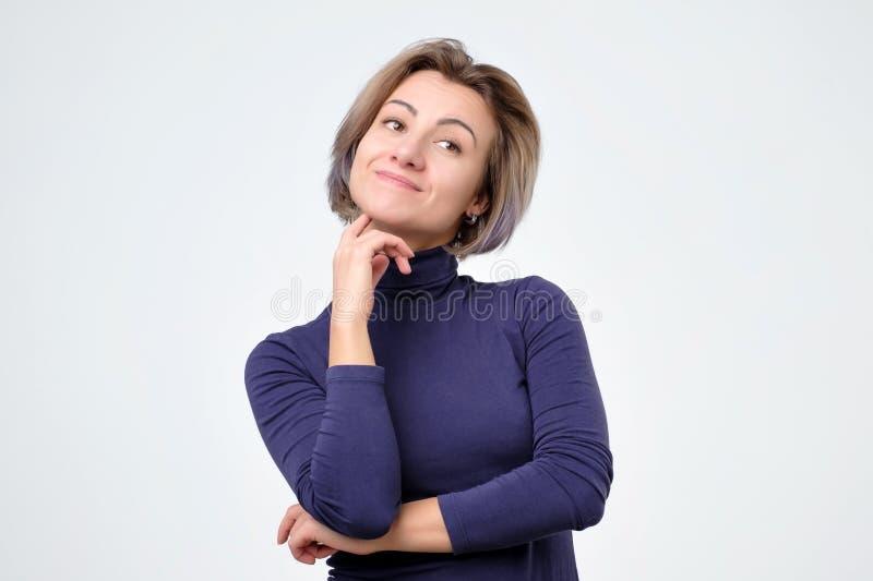 Femme pensant à la chose qu'elle désirent avec l'expression intriguée et intéressée photo stock