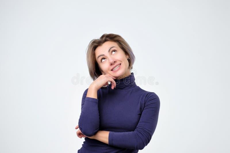 Femme pensant à la chose qu'elle désirent avec l'expression intriguée et intéressée photographie stock