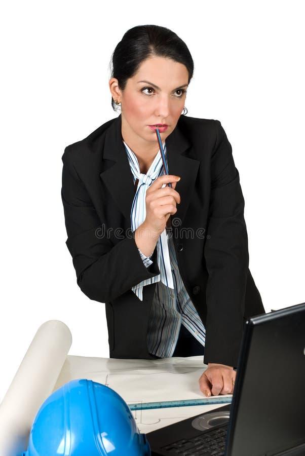 Femme pensante d'ingénieur d'ouvrier dans le bureau photographie stock
