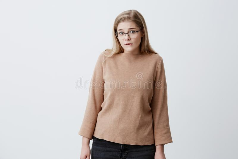 Femme perplexe courbant ses lèvres, regardant l'appareil-photo pensant quelque chose plus d'ou essayant de se rappeler des choses image libre de droits