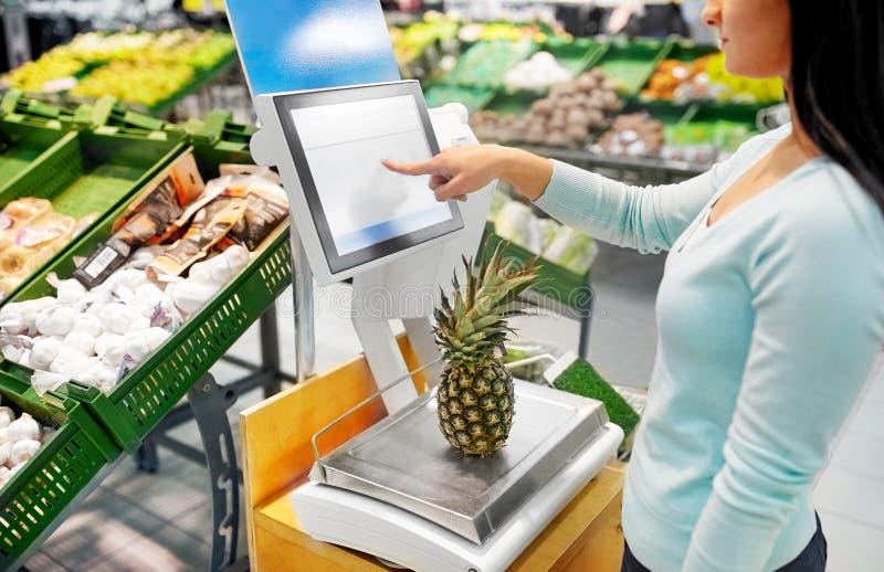 Femme pesant l'ananas sur l'échelle à l'épicerie images libres de droits