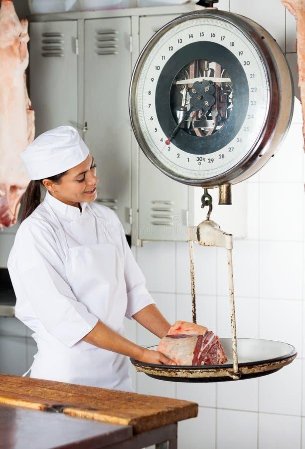 Femme pesant la viande sur l'échelle dans la boucherie image stock