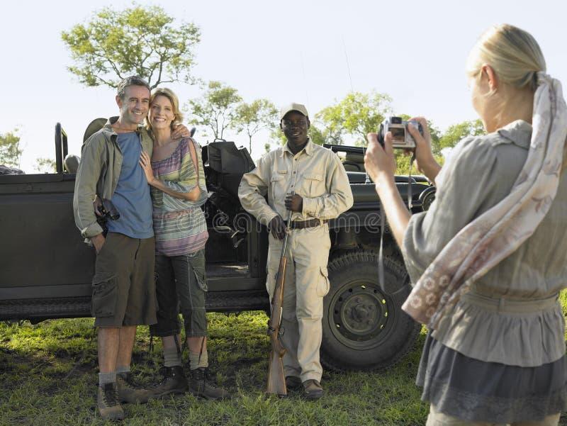 Femme photographiant des couples et guide en la jeep photographie stock