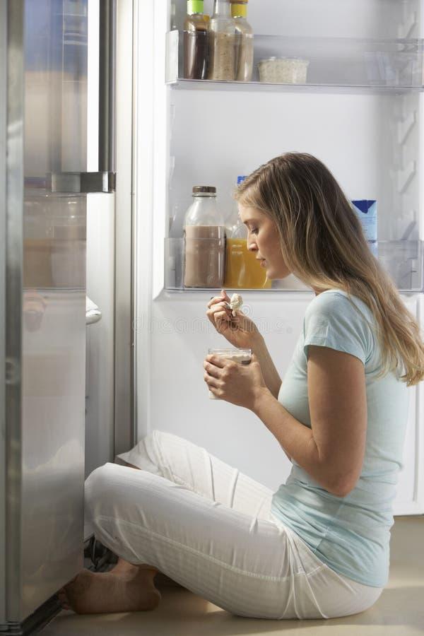 Femme pillant le réfrigérateur la nuit photos libres de droits