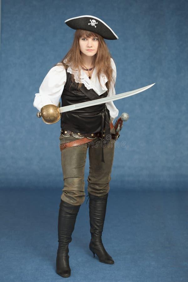 Femme - pirate armé avec un sabre sur le bleu photographie stock