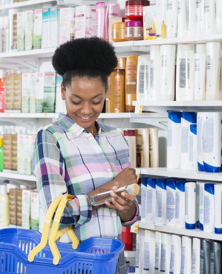 Femme plaçant la bouteille dans le panier à provisions à la pharmacie photo stock