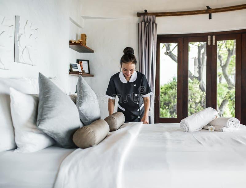 Femme plaçant le lit dans la chambre d'hôtel images stock