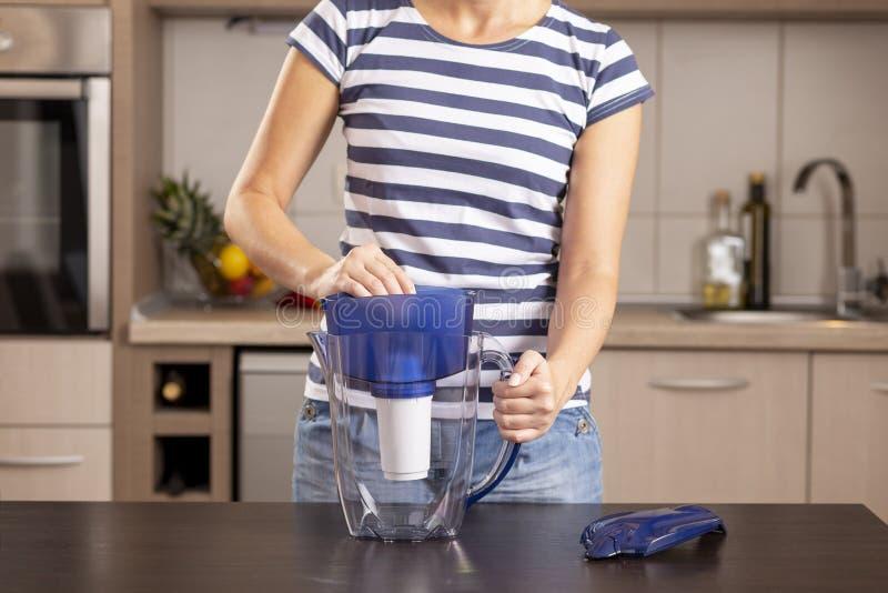 Femme plaçant un nouveau filtre dans un broc de l'eau images libres de droits