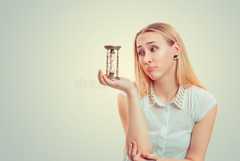 Femme pleine d'espoir regardant le sablier photo libre de droits