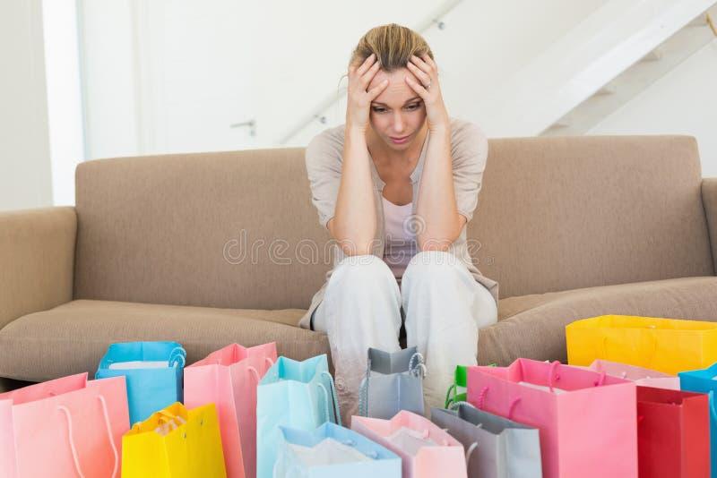 Femme pleine de regrets regardant beaucoup de paniers sur le divan photo libre de droits
