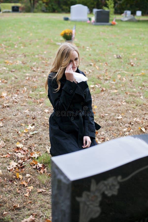 Femme pleurant dans le cimetière photo stock