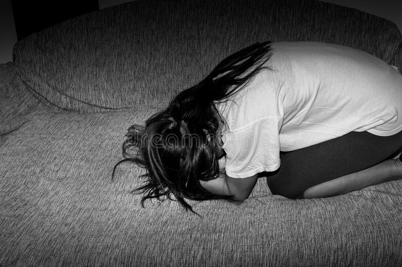 Femme pleurante maltraitée en tant que jeune sentiment diminué et malheureux tandis qu'elle seul s'asseyant dans sa chambre photo stock