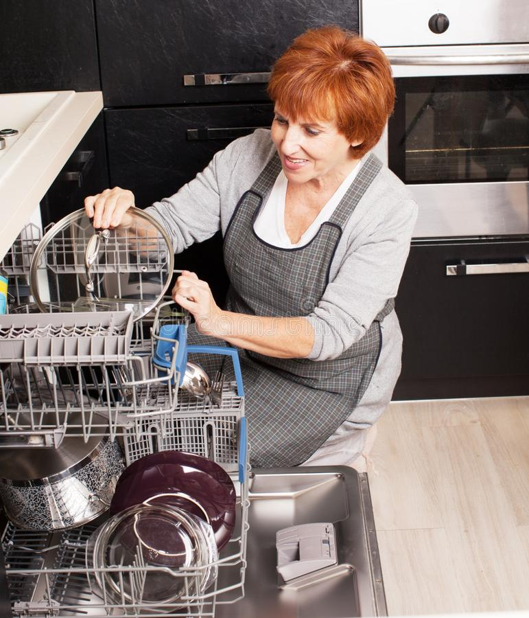 Femme pliant les plats dans le lave-vaisselle images libres de droits