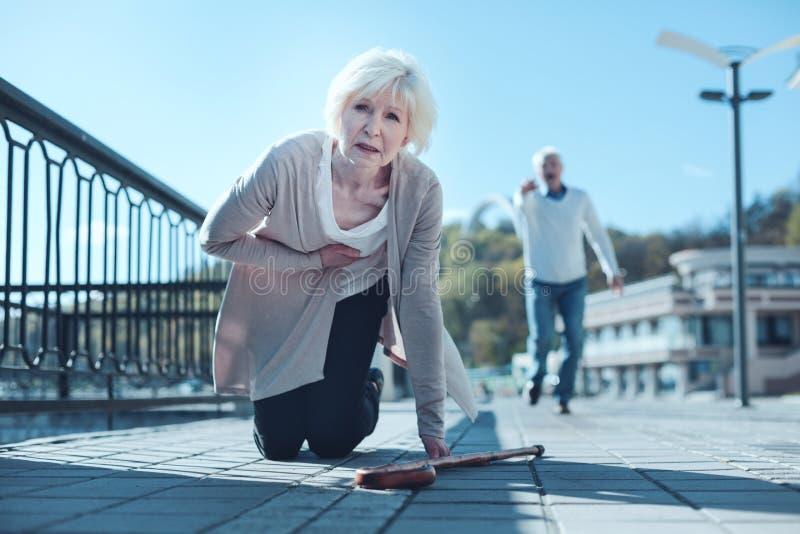 Femme plus âgée épuisée tombant vers le bas avec la crise cardiaque photo stock