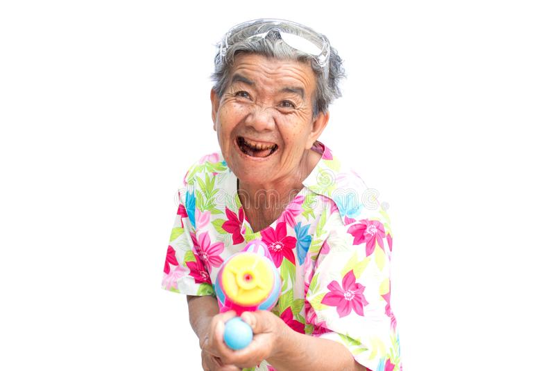 Femme plus âgée asiatique heureuse jouant l'arme à feu d'eau sur le fond blanc photos stock