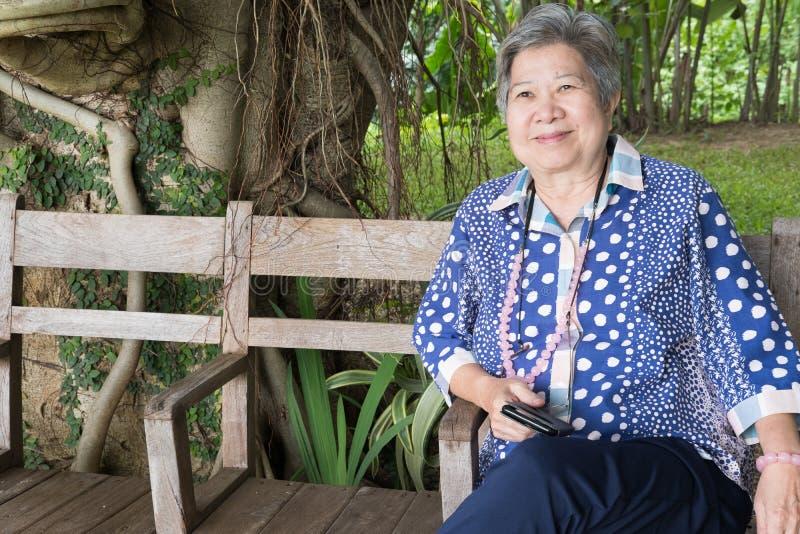 Femme plus âgée asiatique tenant le téléphone intelligent mobile tout en se reposant sur le ch images libres de droits