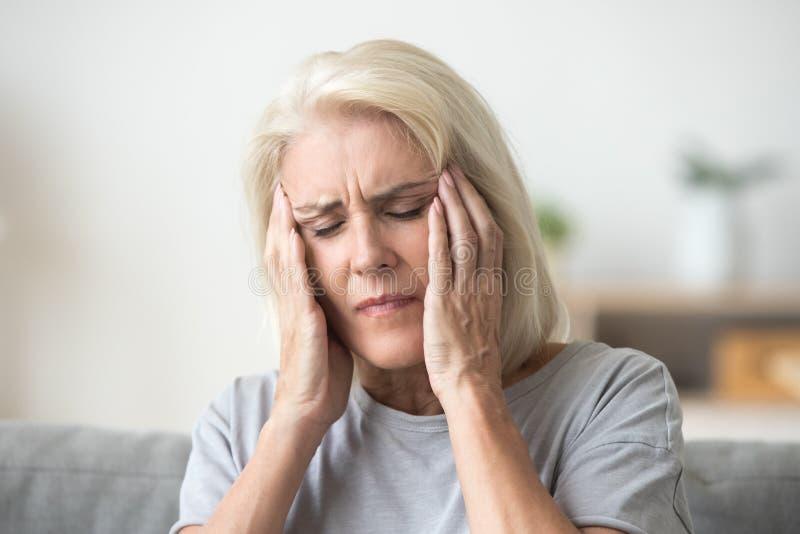 Femme plus âgée bouleversée touchant le sentiment principal douloureux de temples fort il images libres de droits