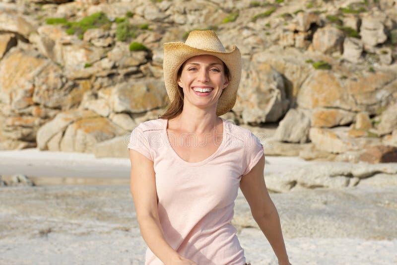 Femme plus âgée de sourire marchant à la plage avec le chapeau images stock