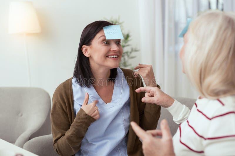 Femme plus âgée exubérante et travailleur social résolvant le puzzle photo stock