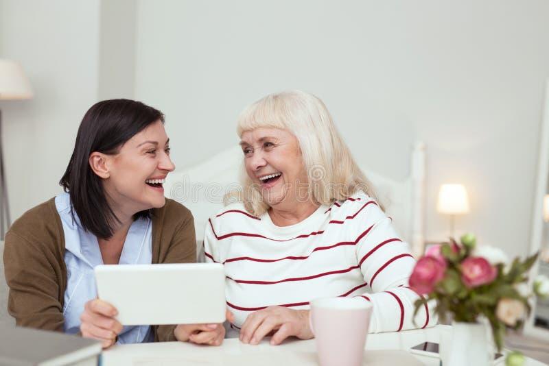 Femme plus âgée gaie et travailleur social jouant sur le comprimé photos stock