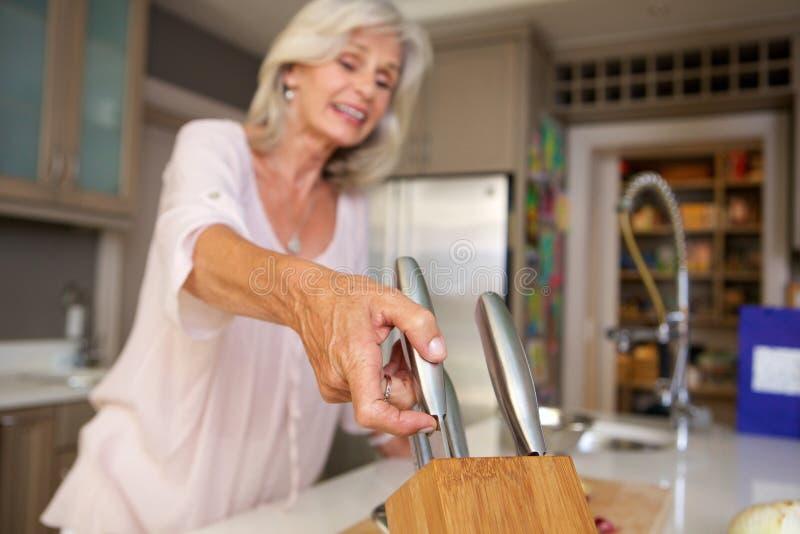 Femme plus âgée heureuse dans la cuisine avec le bloc de couteau photos stock