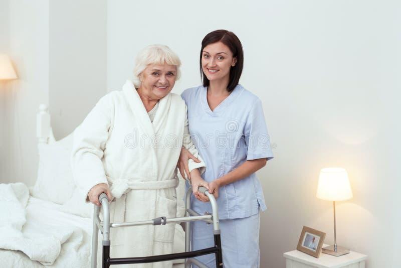 Femme plus âgée joyeuse se tenant avec le marcheur photographie stock