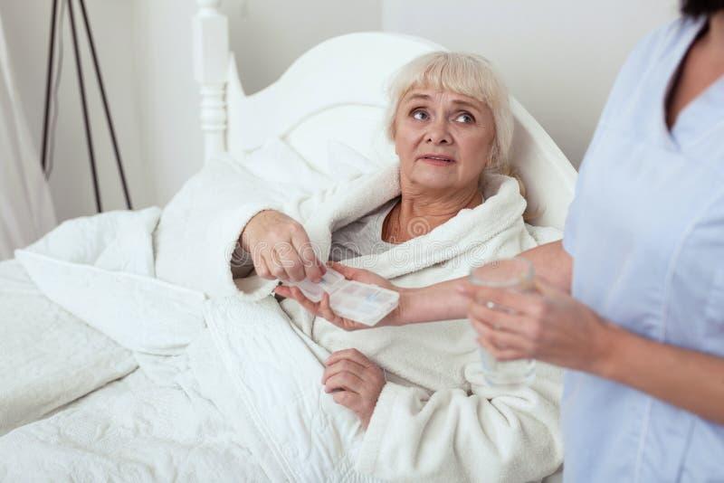 Femme plus âgée mal à l'aise recevant des pilules images stock