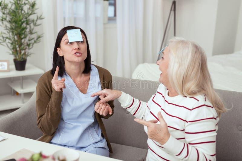 Femme plus âgée optimiste et travailleur social ayant l'amusement images stock