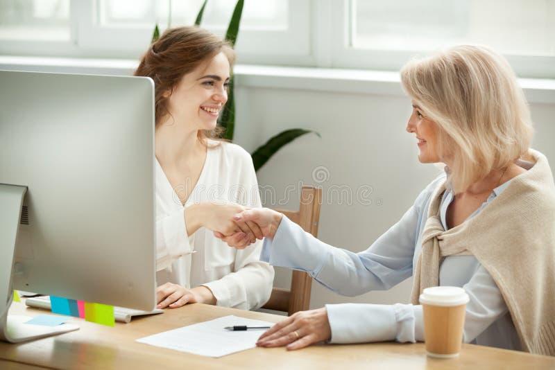 Femme plus âgée satisfaisante et jeune poignée de main de directeur après signin images stock