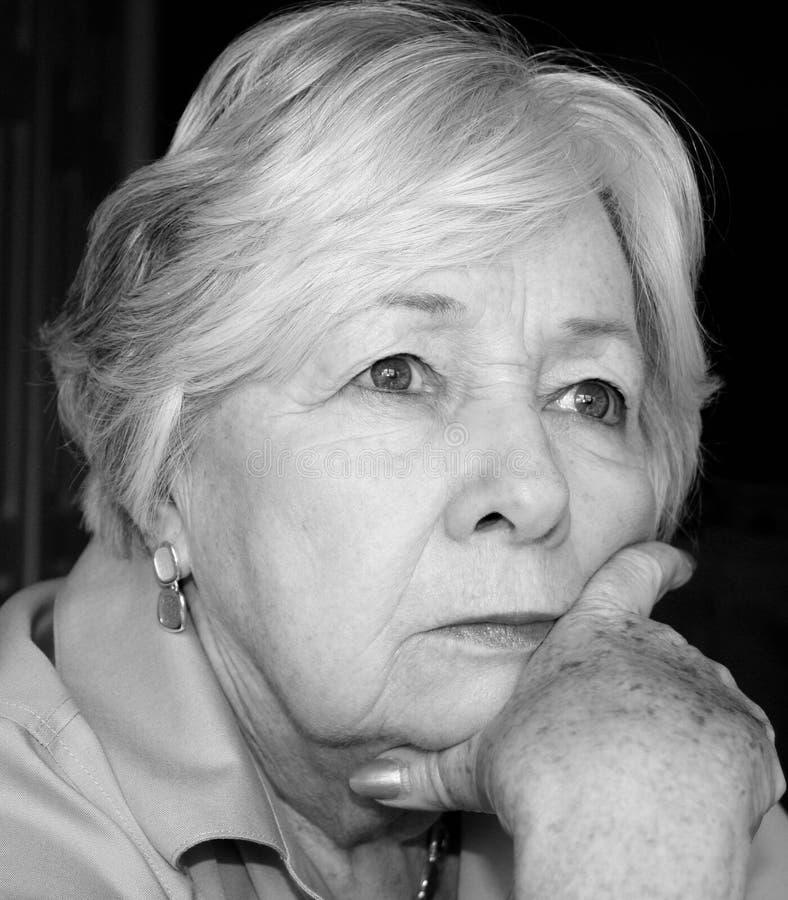 Femme plus âgée songeuse en noir et blanc photographie stock libre de droits
