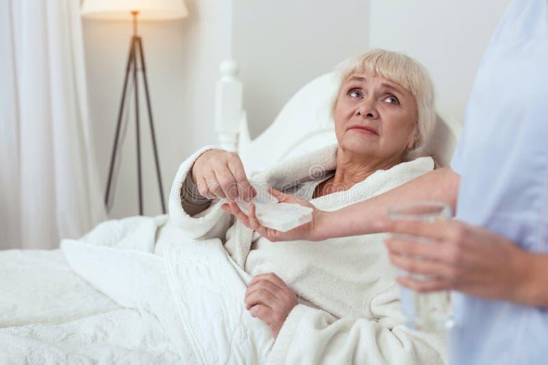 Femme plus âgée triste acceptant des drogues image stock