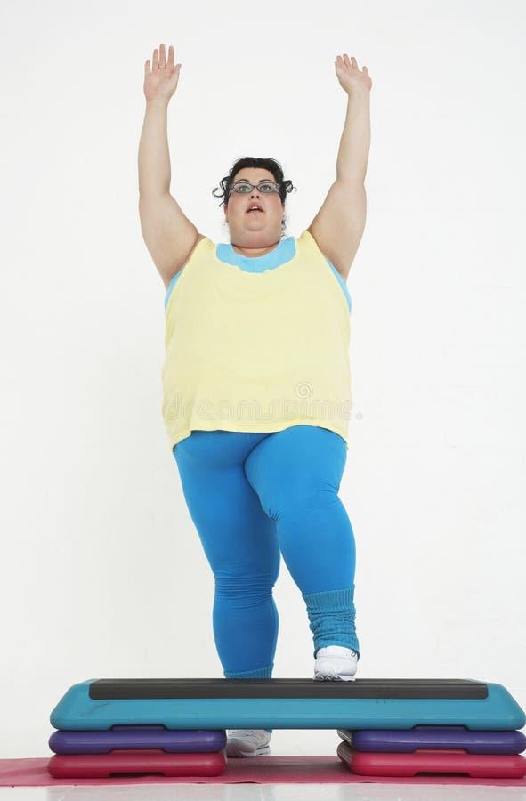 Femme plus de taille sur des étapes d'exercice image stock