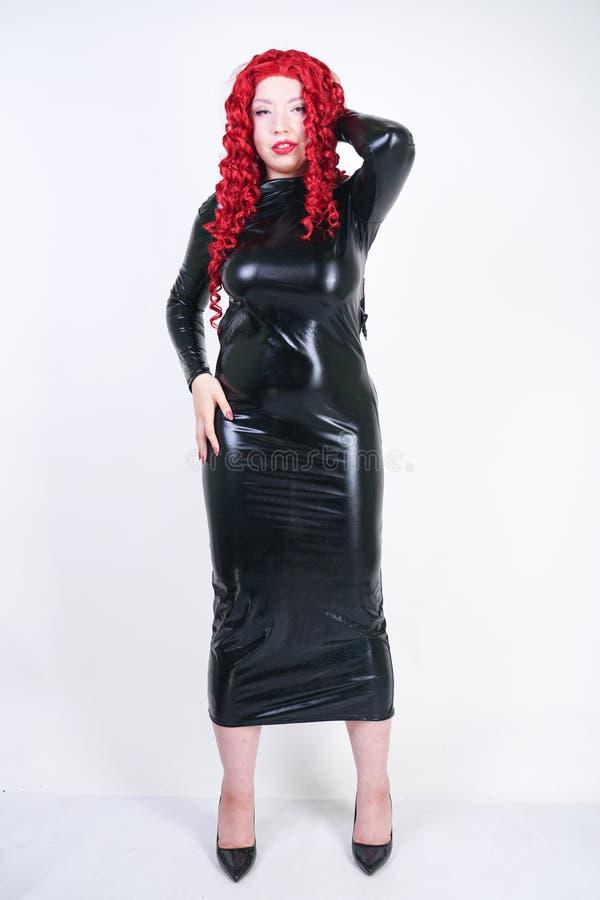 Femme plus luxueuse de taille avec le visage asiatique, le maquillage lumineux et les cheveux bouclés rouges posant dans la longu photo stock