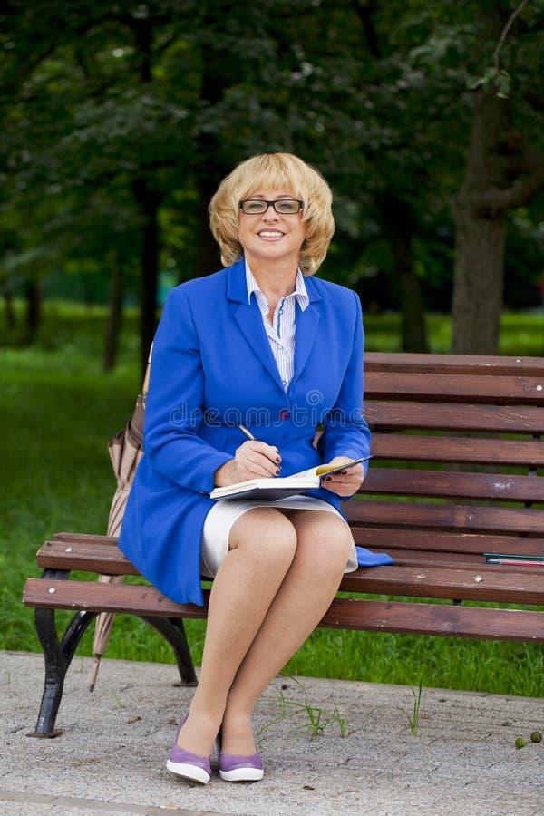 Femme pluse âgé d'affaires dans le sittin de veste sur le banc avec le rondin quotidien photo libre de droits