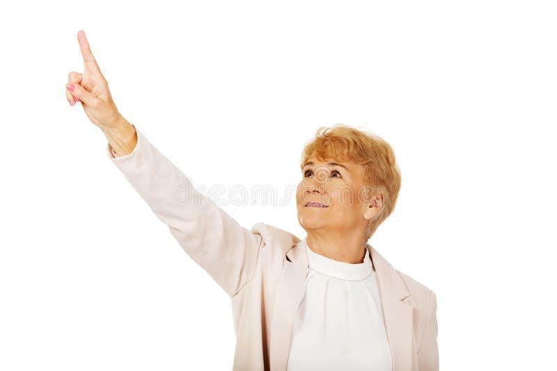 Femme pluse âgé d'affaires de sourire se dirigeant pour le copyspace ou quelque chose images stock