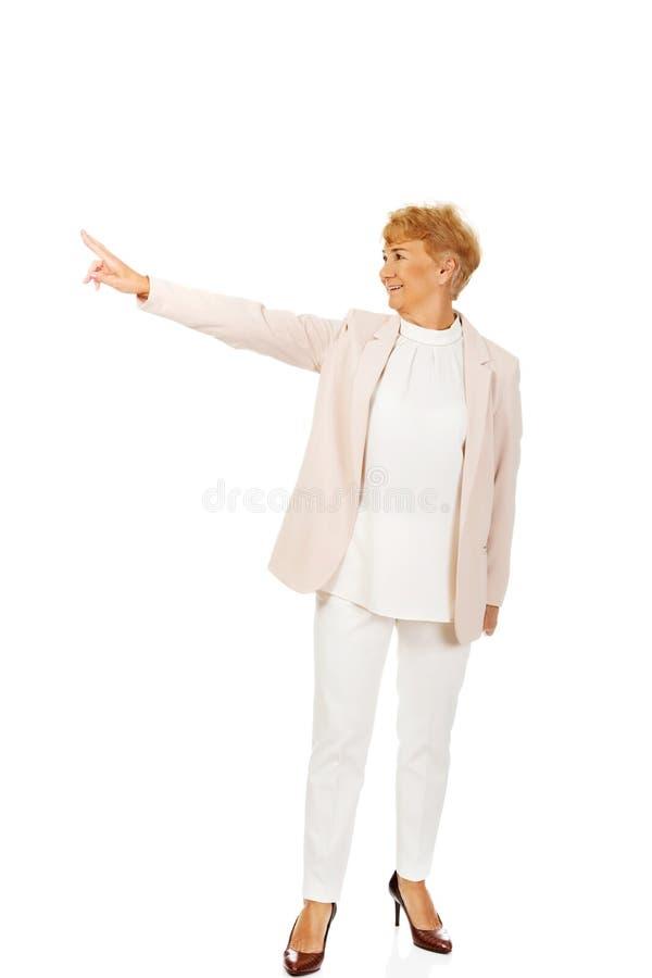 Femme pluse âgé d'affaires de sourire se dirigeant pour le copyspace ou quelque chose photographie stock