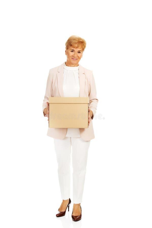 Femme pluse âgé d'affaires de sourire tenant la boîte en carton photographie stock