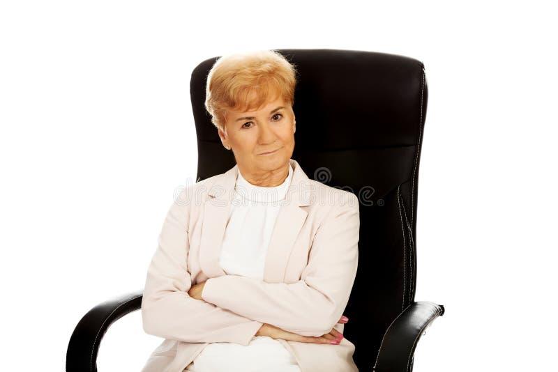 Femme pluse âgé fâchée d'affaires s'asseyant sur le fauteuil avec les bras pliés photographie stock libre de droits