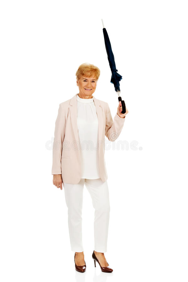 Femme pluse âgé heureuse d'affaires se dirigeant avec le parapluie image stock