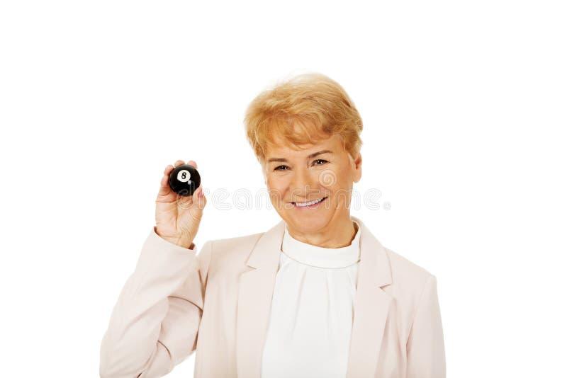 Femme pluse âgé heureuse d'affaires tenant la billard-boule huit photo stock