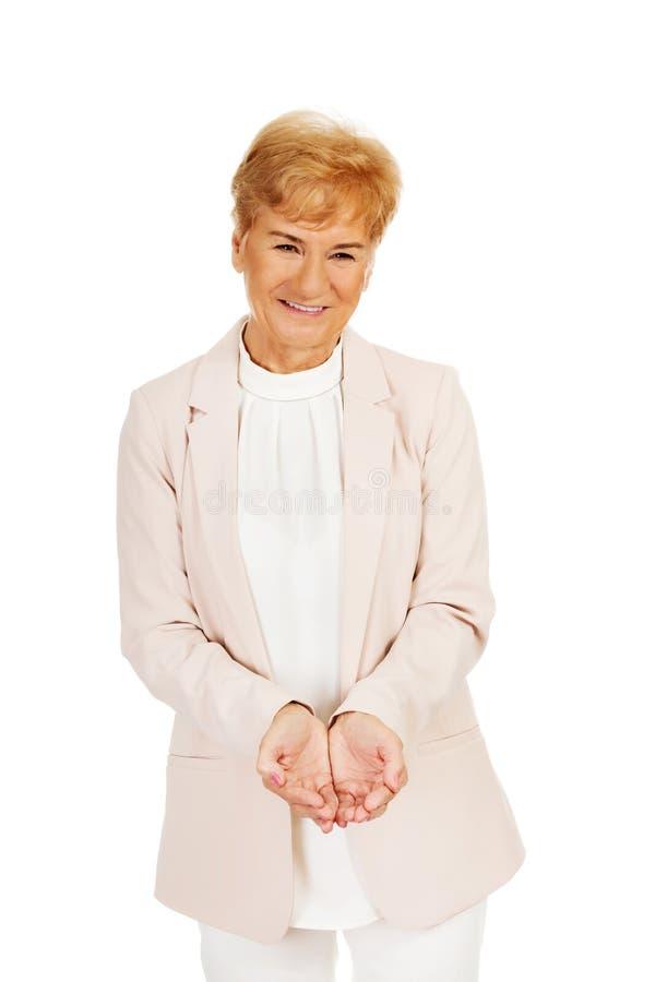 Femme pluse âgé heureuse d'affaires tenant le copyspace ou quelque chose sur les paumes ouvertes photographie stock