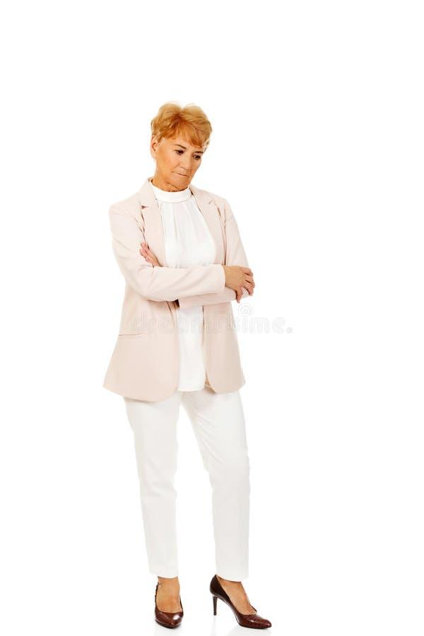 Femme pluse âgé inquiétée d'affaires avec des bras pliés photos stock