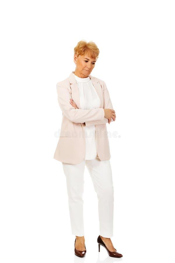 Femme pluse âgé inquiétée d'affaires avec des bras pliés image libre de droits