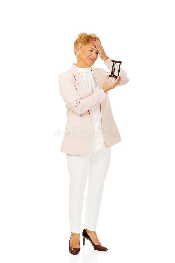 Femme pluse âgé inquiétée d'affaires avec la paume sur son front tenant le sablier photo libre de droits