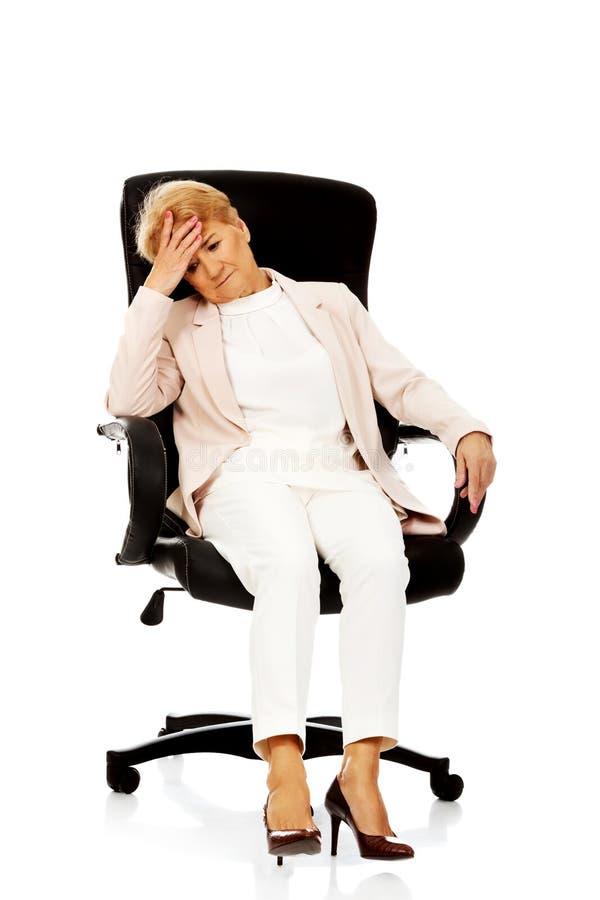 Femme pluse âgé inquiétée d'affaires s'asseyant sur le fauteuil image libre de droits