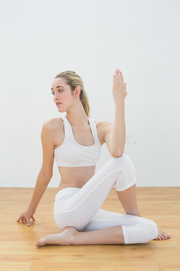 Femme ponytailed sérieuse s'asseyant sur le plancher étirant son corps image stock