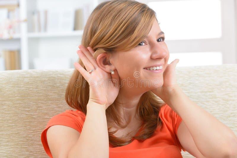 Femme portant l'aide sourde image stock
