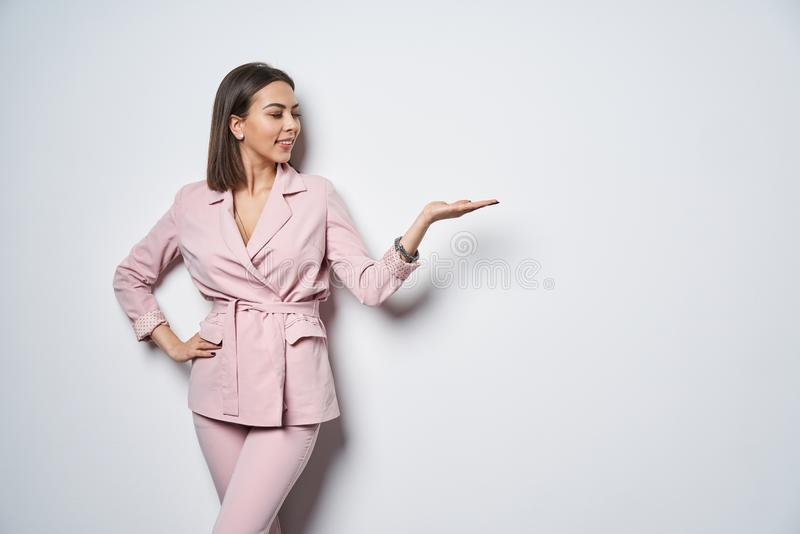 Femme portant l'espace rose de copie de participation de costume sur la paume photographie stock