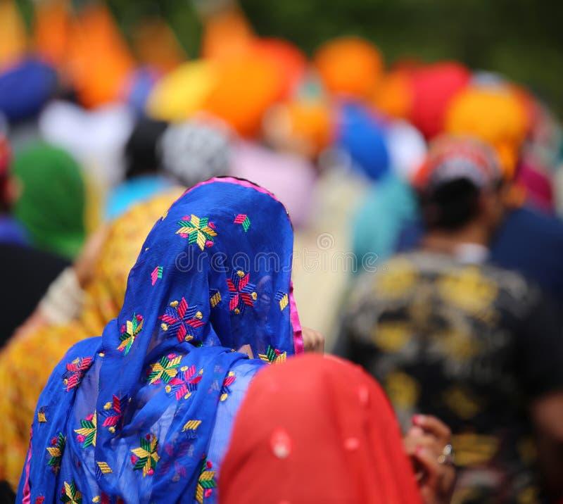 femme portant la coiffe bleue de voile pendant une réunion des personnes image stock