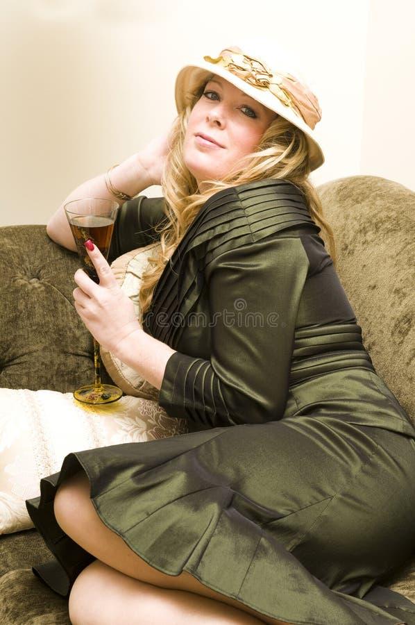 Femme portant la jolie robe sirotant un cocktail photographie stock